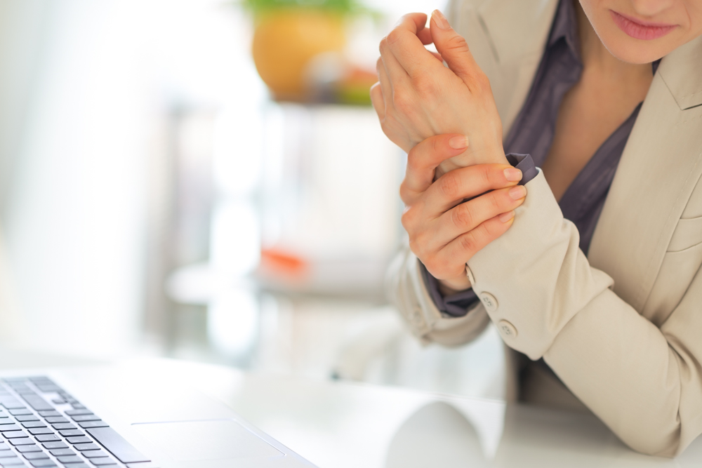 woman holding wrist in pain from carpal tunnel syndrome
