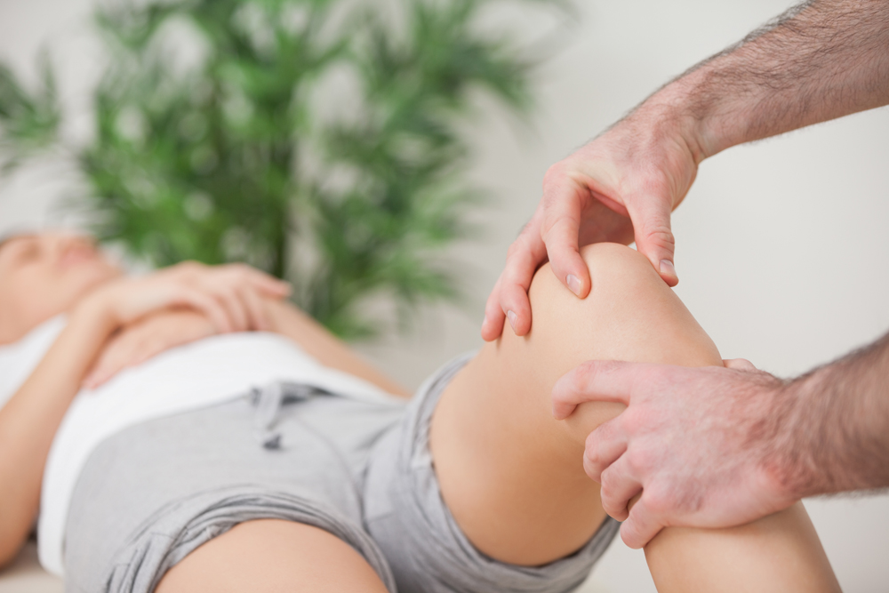 Woman with knee pain getting chiropractic care.